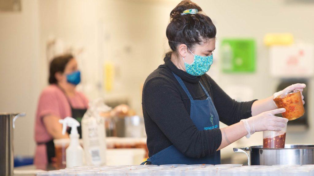 Volunteer wearing a mask working in the ktichen.