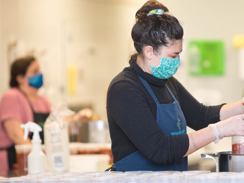 Volunteer wearing a mask working in the ktichen.