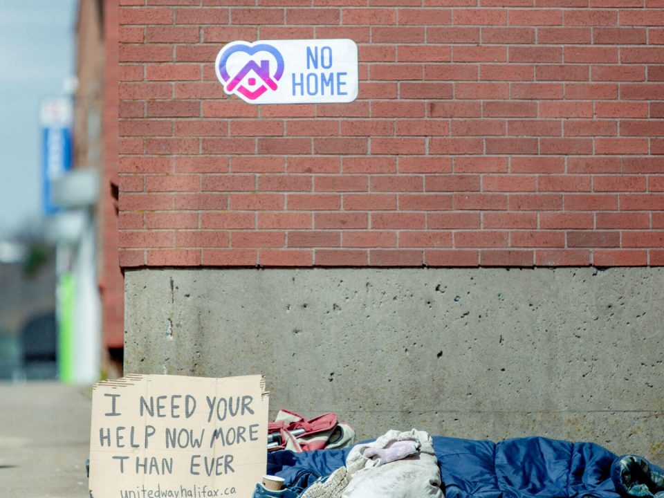 Homeless person's belongings (sleeping bag, shoes, blankets and bag) on the street next to a cardboard sign reading