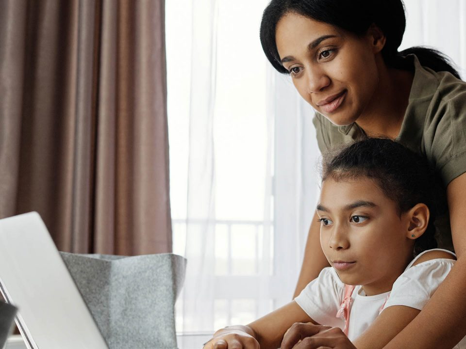 (Stock photo) Parent and child looking at computer screen.