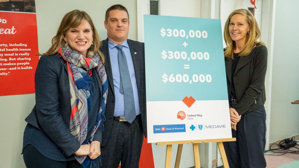 United Way staff and donors stand next to a board celebrating a $600,000 donation
