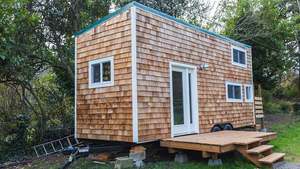 Portable tiny home with wood siding in the back yard of a larger property. Forest Grove, Oregon, USA.
