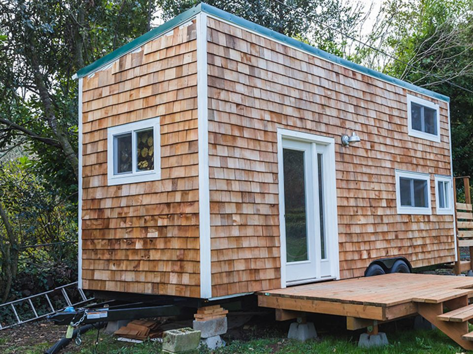 A portable tiny home (like the ones approved in Halifax) with wood siding in the back yard of a larger property. Forest Grove, Oregon, USA.