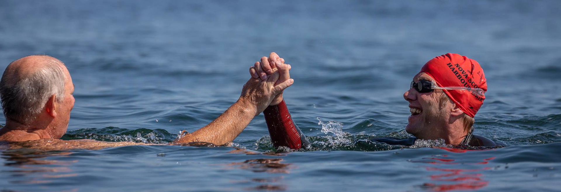 Swimmers high-fiving in the Halifax Harbour