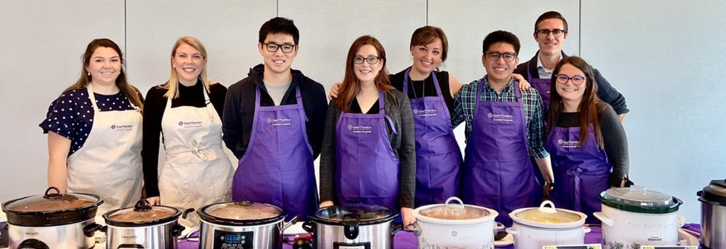 Eight volunteers wearing aprons, standing behind a table with food cooking.