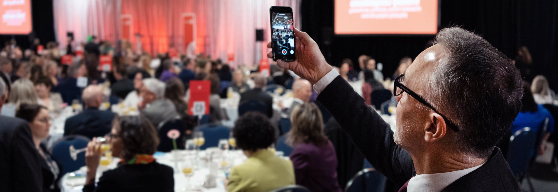 Person taking photo with their cell phone of a busy gala dinner.