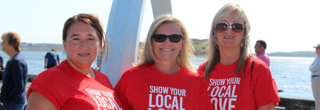 Three United Way volunteers standing on the Halifax pier wearing red shirts.