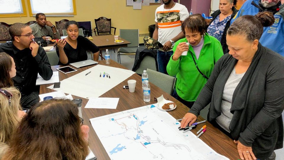 Community members look at project plans in a conference room.