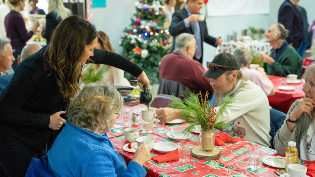 Person refilling a guest's coffee mug at a Christmas breakfast.