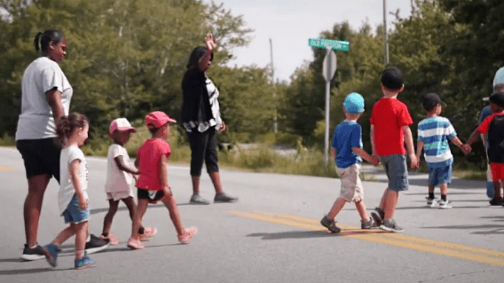 Children crossing the street in East Preston while a chaperone holds traffic.