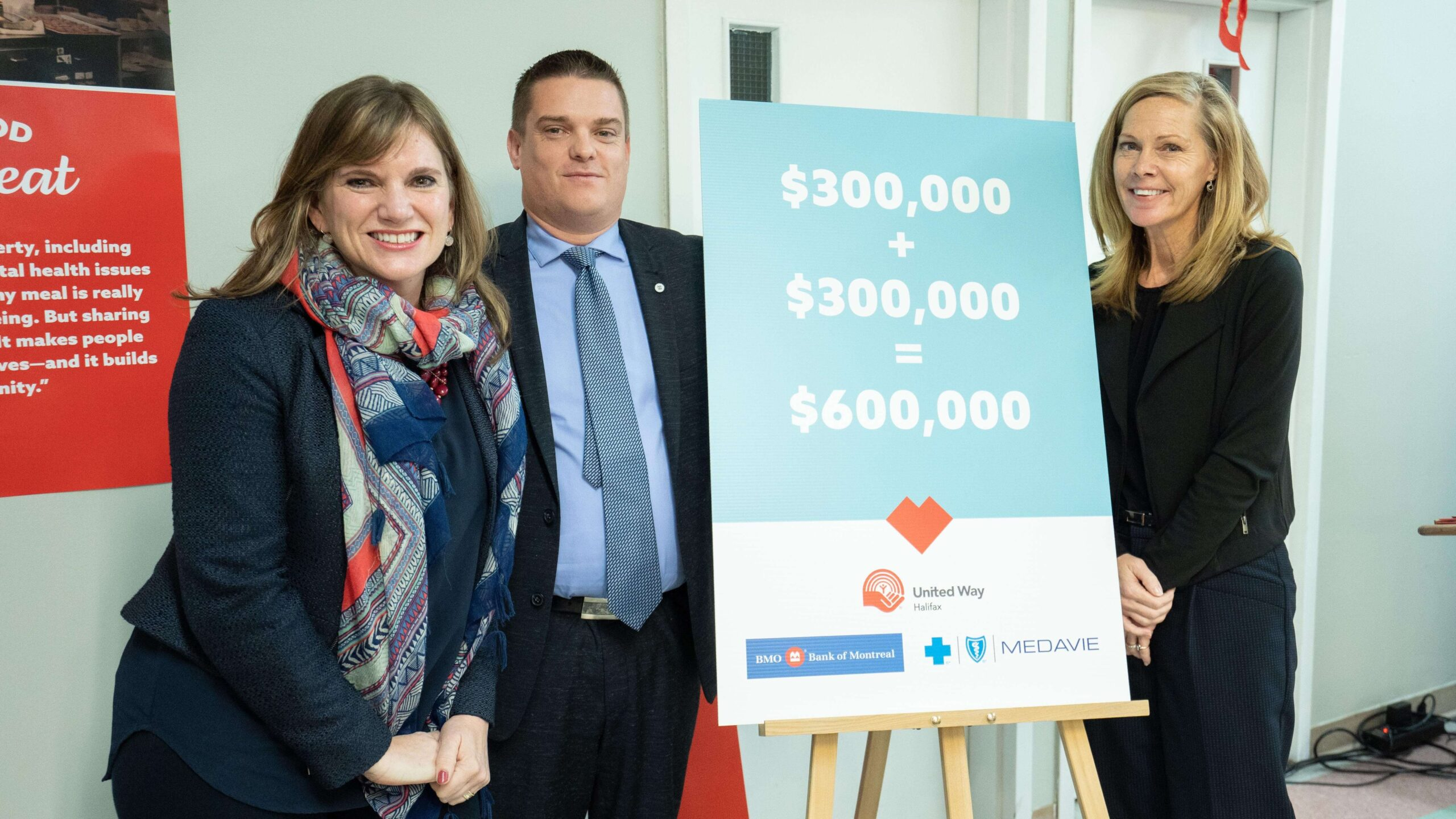 Three people stand around a sign that says $600,000