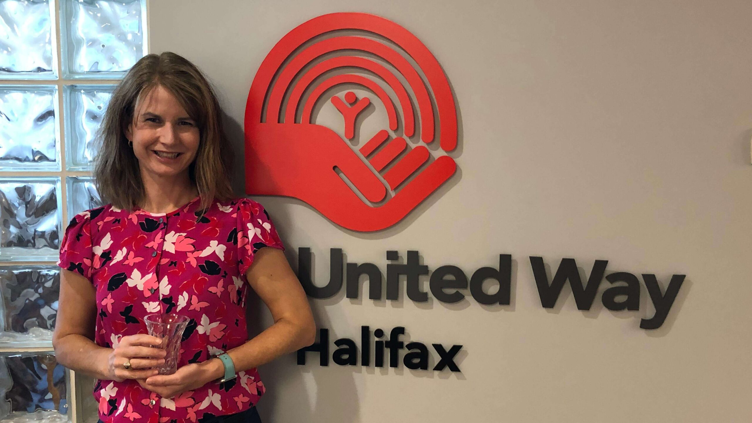 Woman standing beside United Way Halifax sign