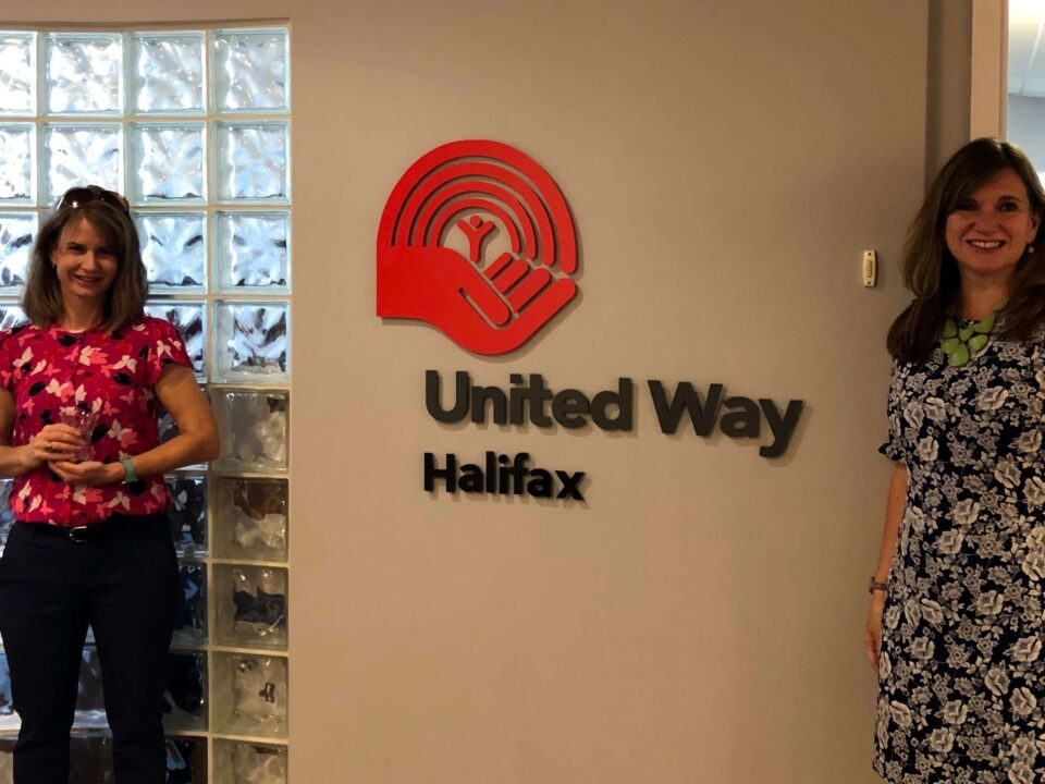 Two women standing on either side of a United Way Halifax sign