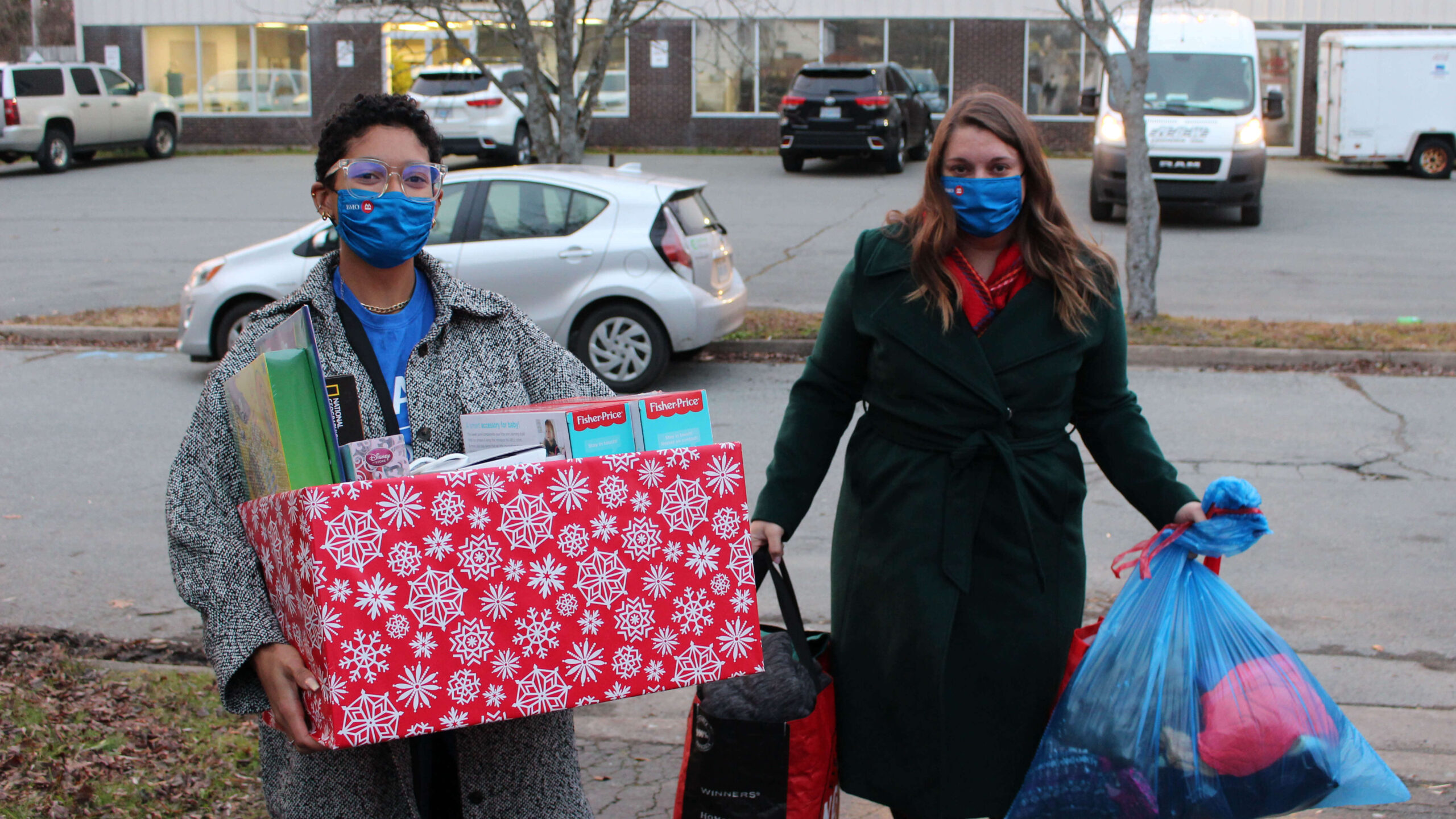 Volunteers carry a box of gift and bag of donated clothes