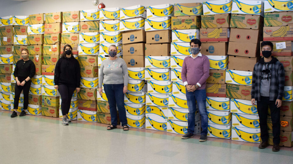 Volunteers stand in front of Christmas hampers for community