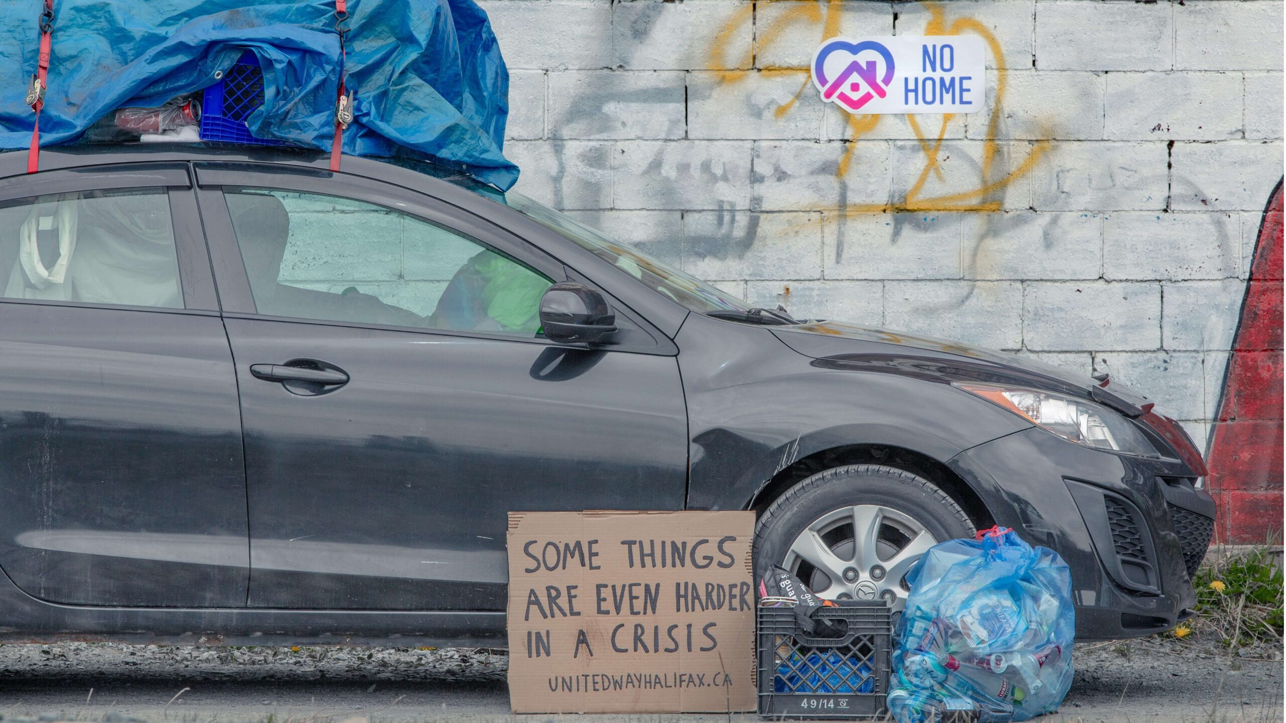 """A car with tarp covering belongings on the roof, and bags of recycling around it. Sticker on the graffitied wall behind says """"no home"""" and a cardboard sign says """"some things are."""" even harder in a crisis"""