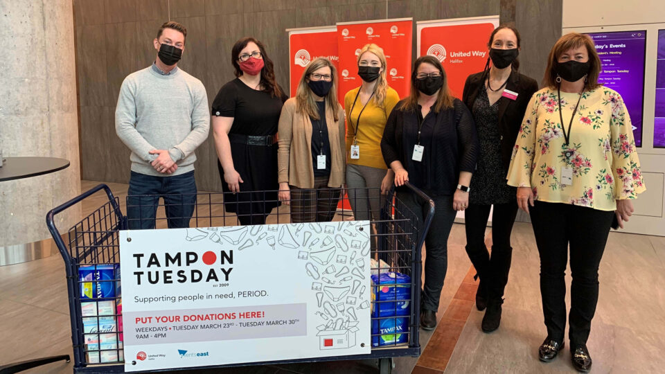 group of people wearing masks around big container of menstrual products