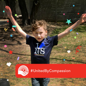 9 year old Levi runs through a finish line with his hands in the air. A red tag on the photo reads: United By Compassion
