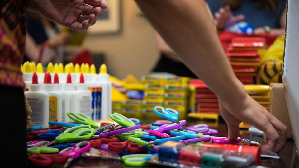 Volunteers pack school supplies