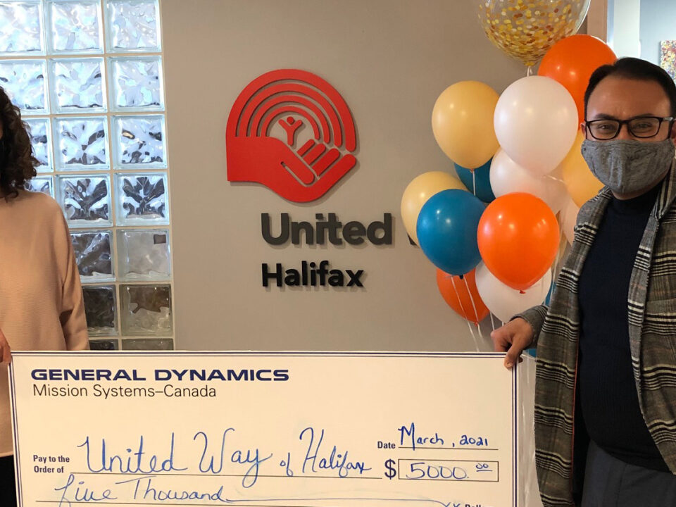 United Way staff member Ambuj accepts a large cheque from a coprorate partner