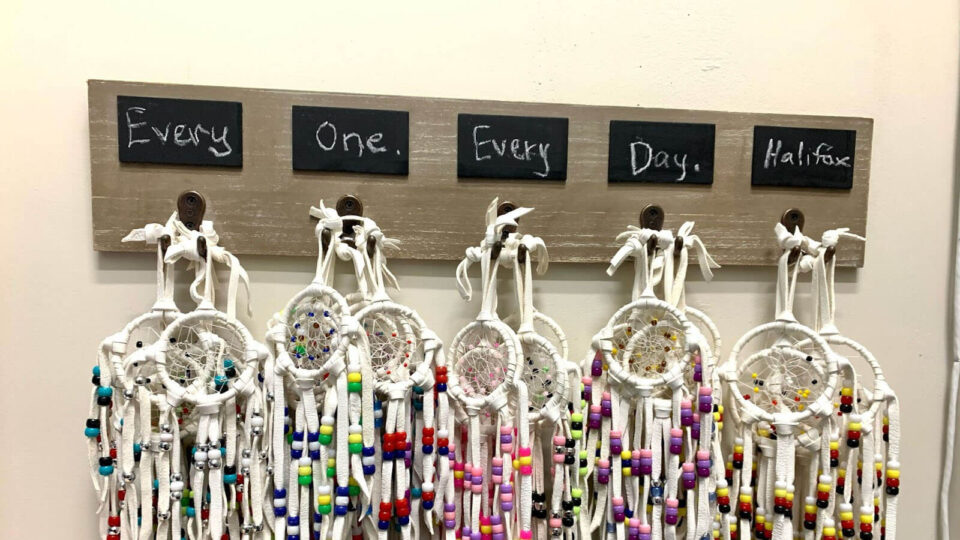 Colourful dream catchers hanging on a wall underneath the text 'Every One Every Day Halifax' written in chalk