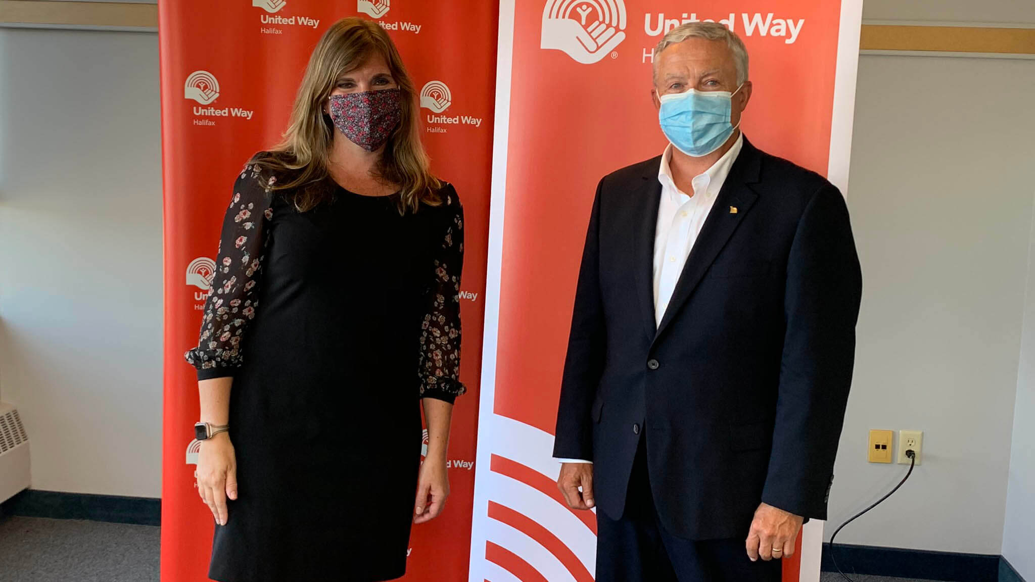 United Way Halifax CEO Sara Napier and Board Chair Craig Thompson stand, wearing masks, in front of red United Way banners