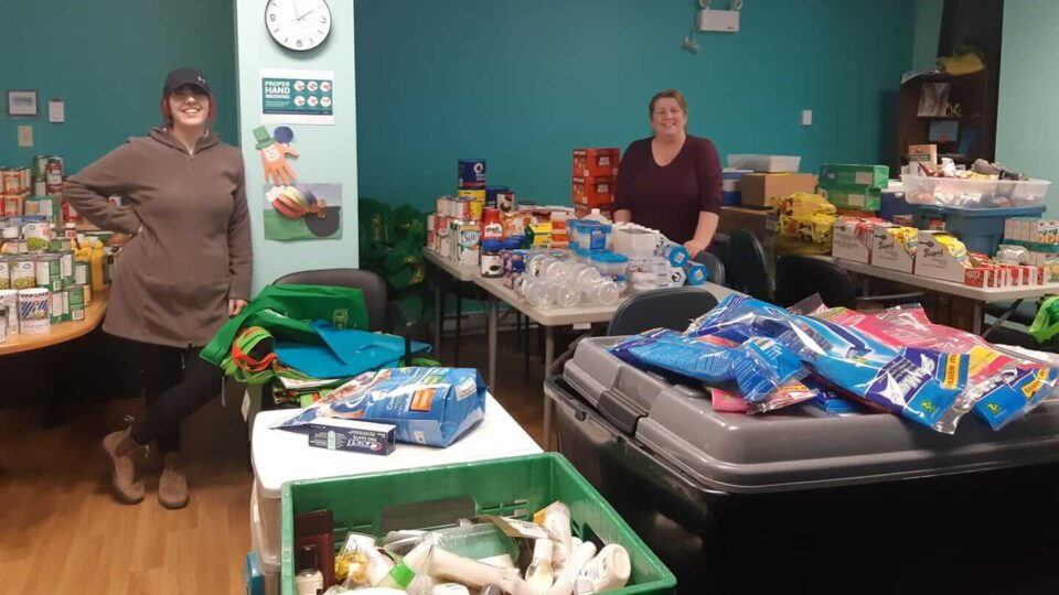 Two women stand in a room with tables full of food and toiletries