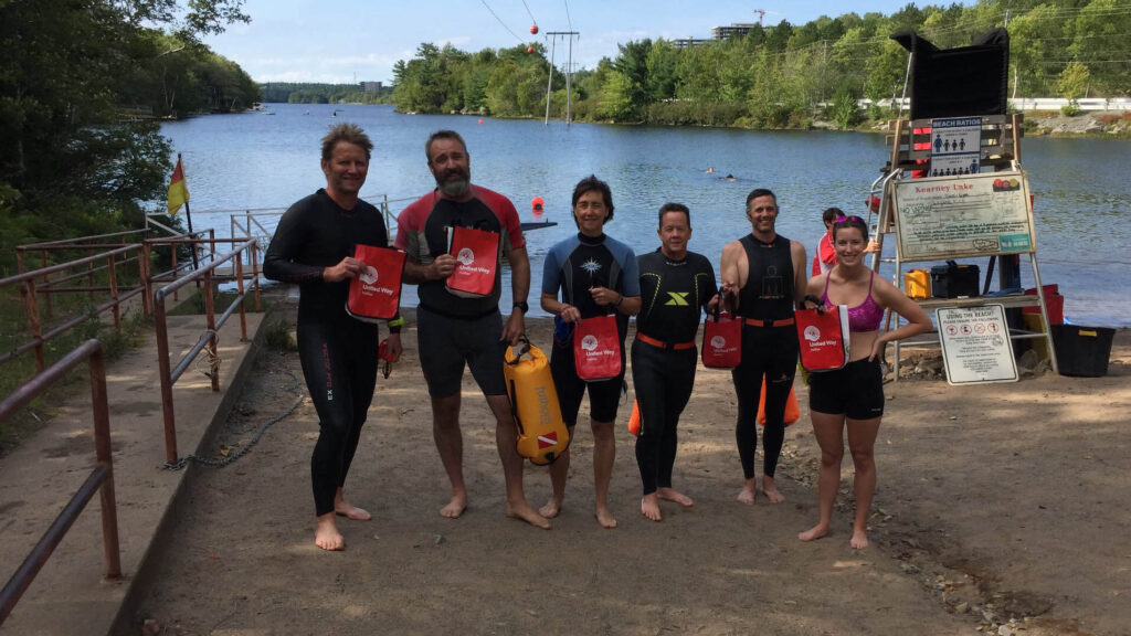 Six swimmers stand in front of a lake holding United Way bags