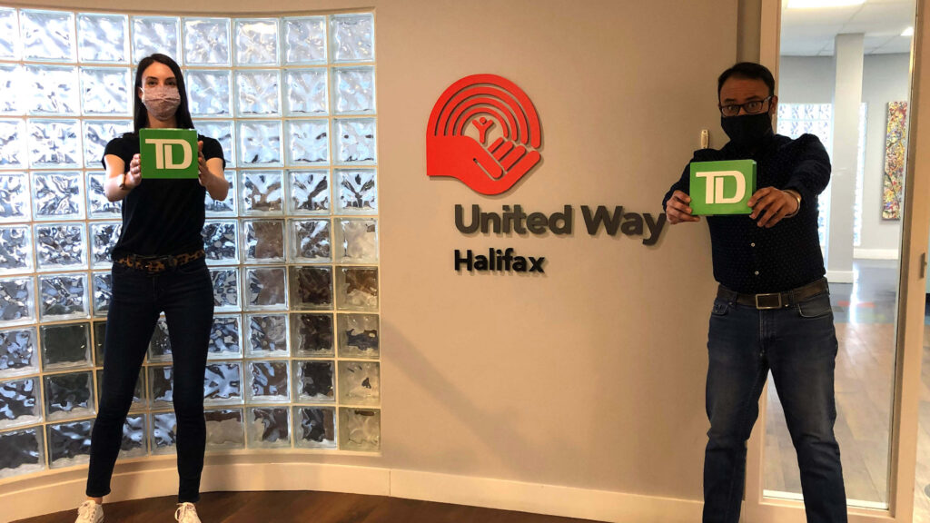 United Way Halifax staff hold green TD boxes in front of the United Way Halifax logo