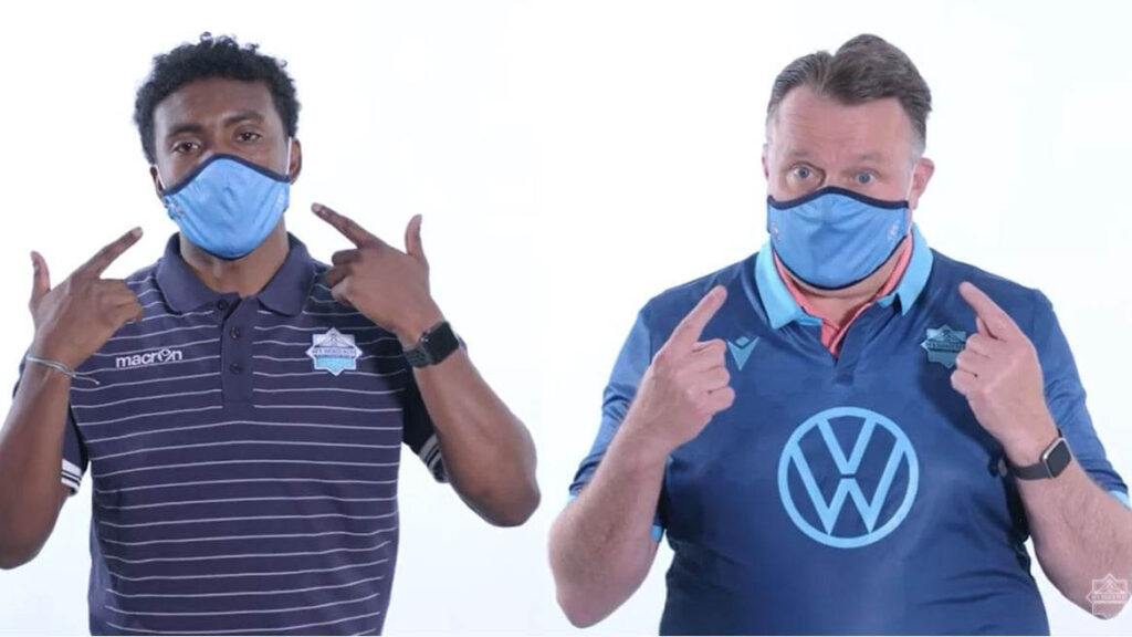 Two men wearing Halifax Wanderers shirts and face masks