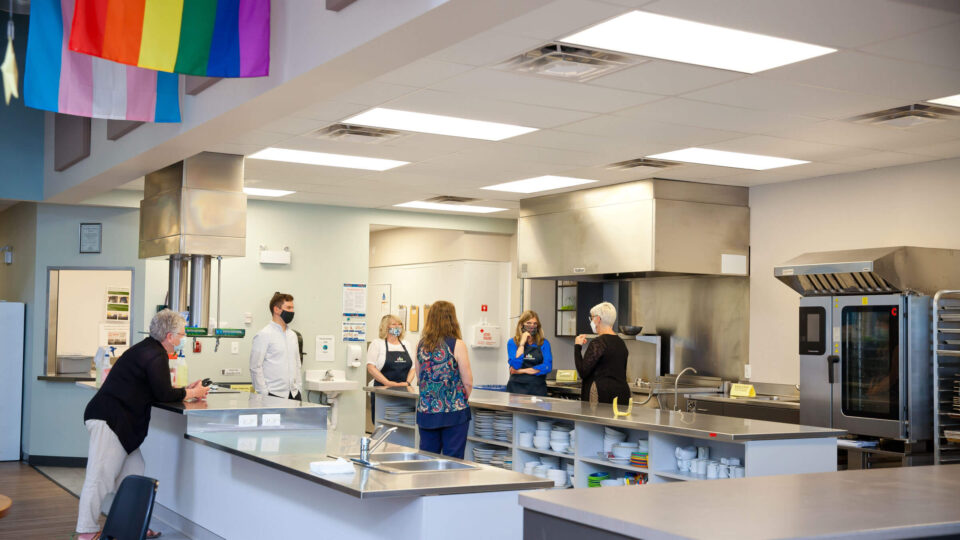 People standing distanced apart in a commercial kitchen