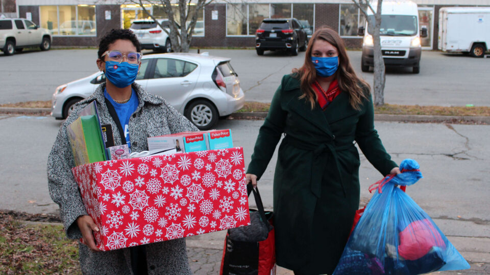 Two volunteers carry boxes and bags with gifts and clothing