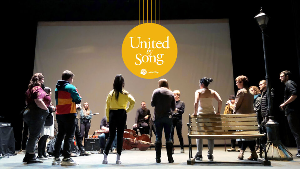 A group of people stand in a circle around a stage with a lamp post and bench on the right hand side with their backs facing the camera. The yellow 'United by Song' logo is in the top middle of the image.