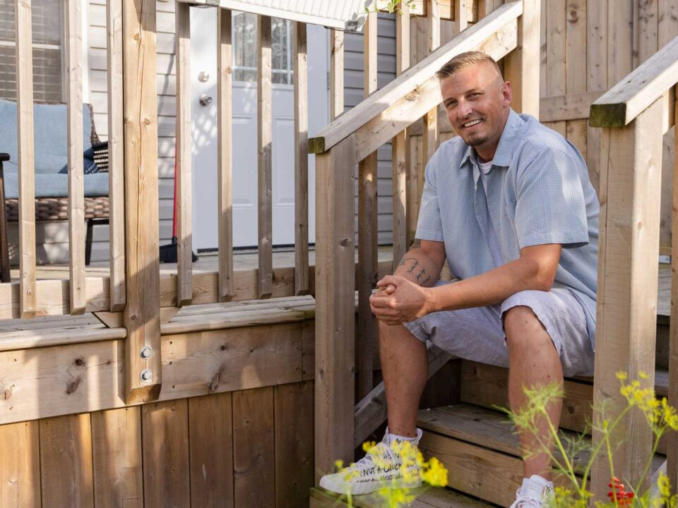 A person sitting on the front steps of their home smiling