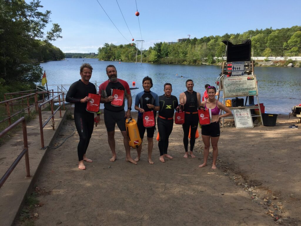 Group of six people wearing wetsuits in front of a lake