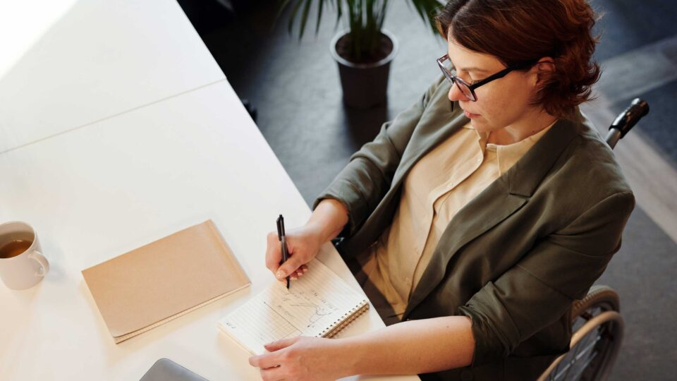 Person sitting at a desk with pen and paper