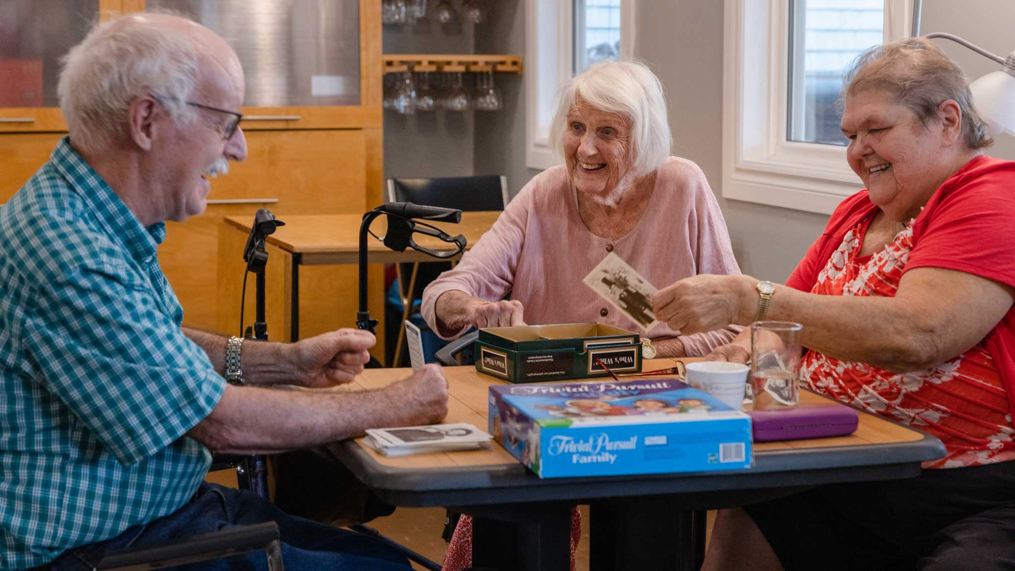 3 seniors sitting around a table playing a trivia game and laughing