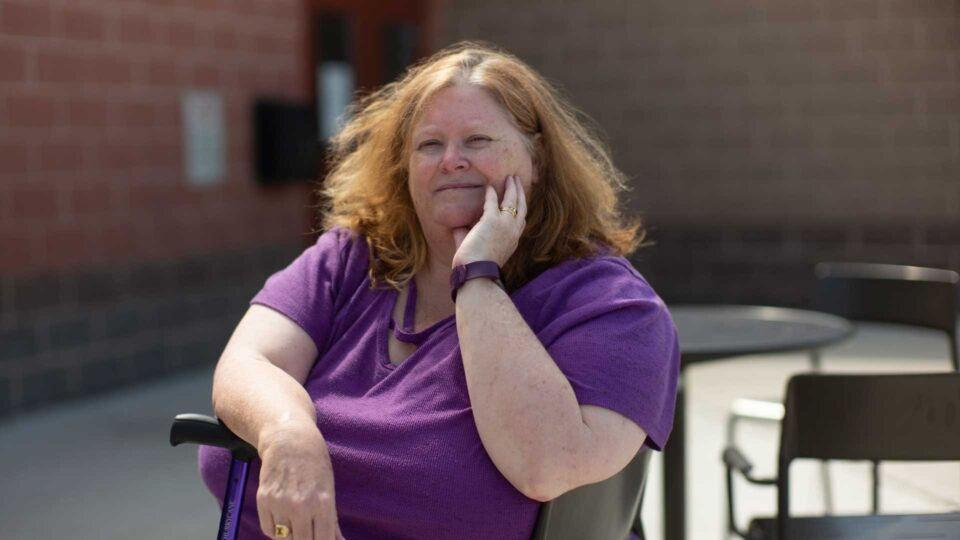 United Way donor, Heather sits outside